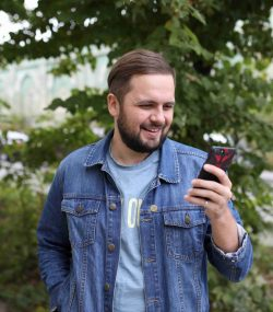man-in-a-denim-jacket-looks-at-the-phone-screen-an-UQLAY79