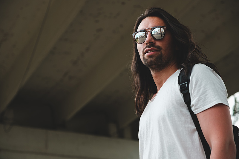 Low angle shot of man model wearing fashionable sunglasses reflecting the city. Attractive man with long hair and small beard wearing white t-shirt and backpack smiling. Copy space on right.