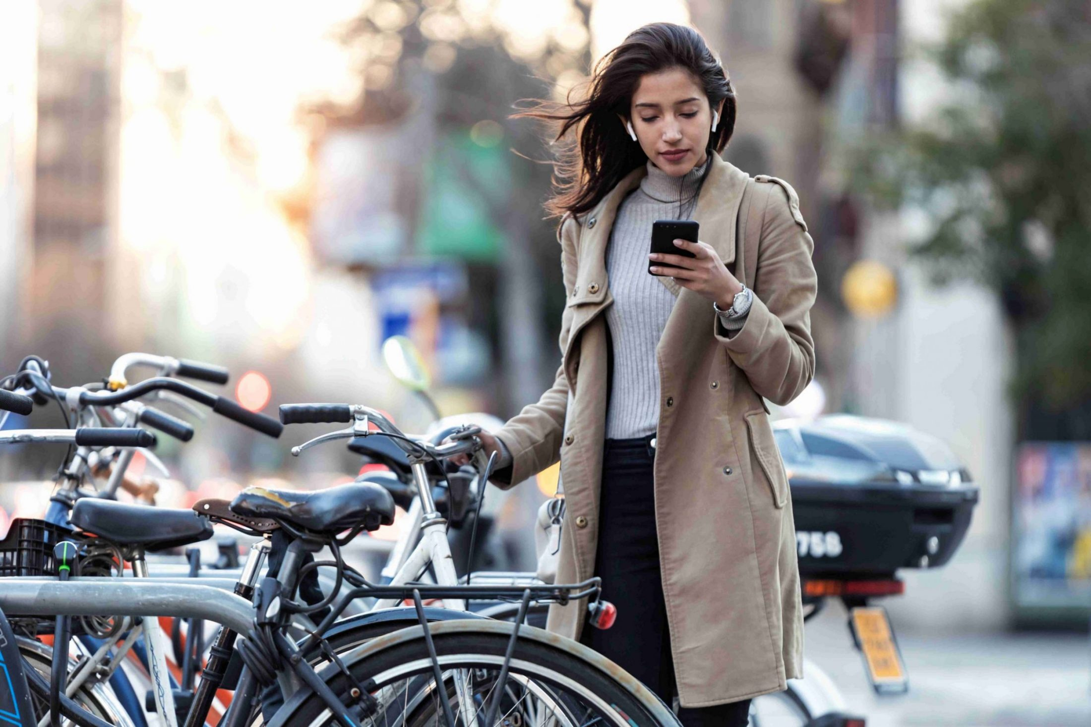 Shot of pretty young woman consulting the map on her mobile phone before taking the bicycle on the street.
