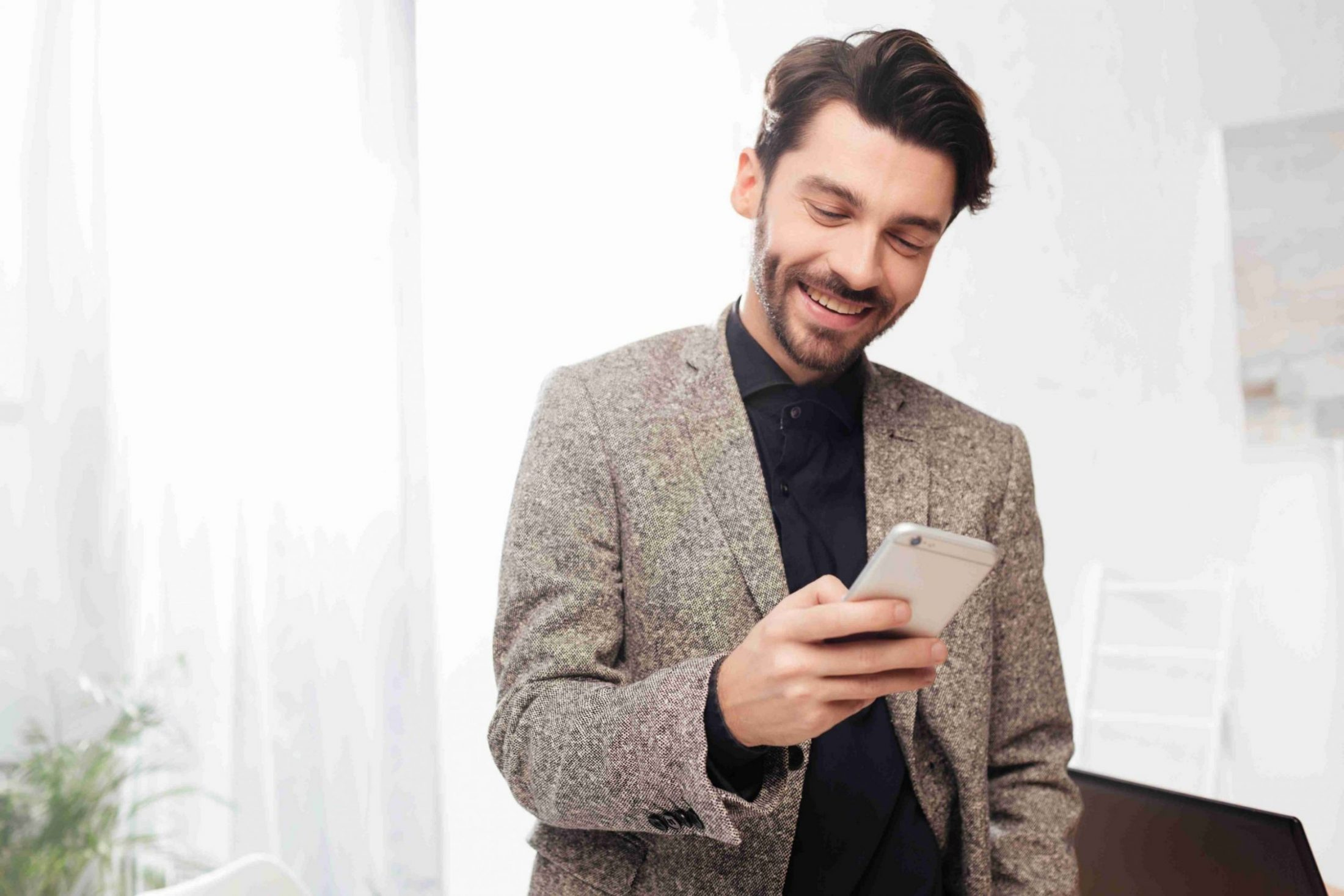 Portrait of young smiling businessman in black shirt and jaket standing and happily looking in cellphone in office isolated